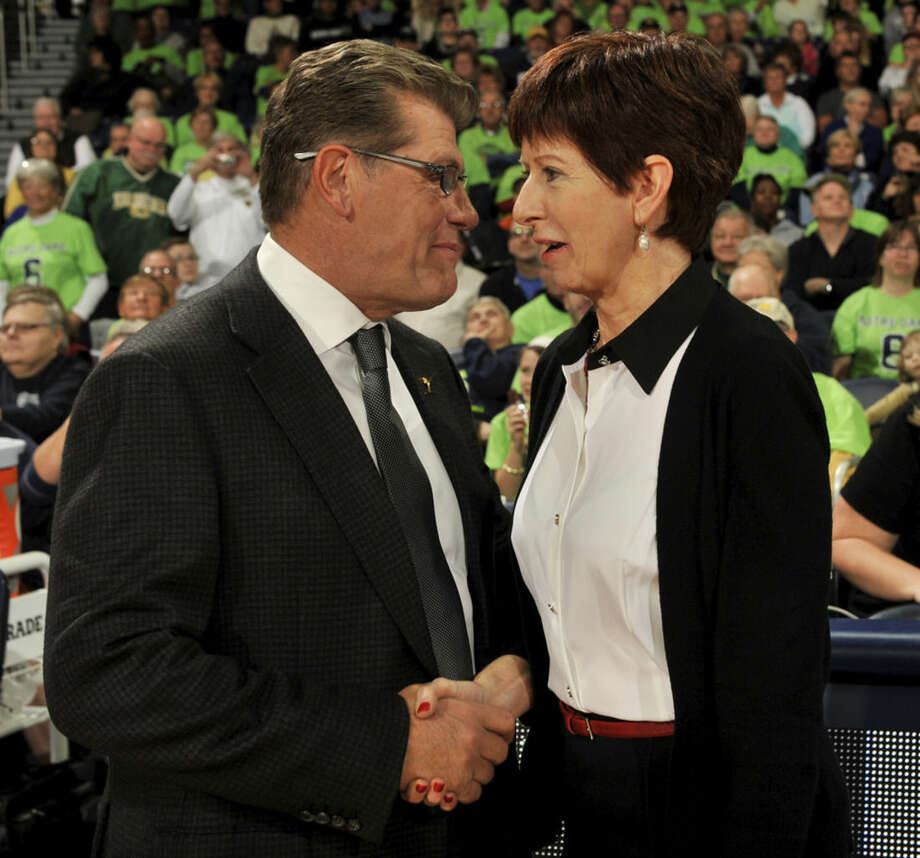 Notre Dame coach Muffet McGraw, right, and Connecticut coach Geno Auriemma talk before an NCAA college basketball game, Saturday Dec. 6, 2014, in South Bend, Ind. (AP Photo/Joe Raymond)