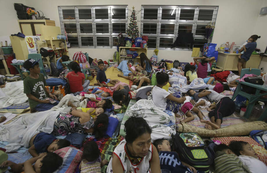 Filipino families seek refuge at a school used as an evacuation center as they prepare for Typhoon Hagupit in Legazpi, Albay province, eastern Philippines Saturday, Dec. 6, 2014. Typhoon Hagupit slammed into the central Philippines' east coast late Saturday, knocking out power and toppling trees in a region where 650,000 people have fled to safety, still haunted by the massive death and destruction wrought by a monster storm last year. (AP Photo/Aaron Favila)