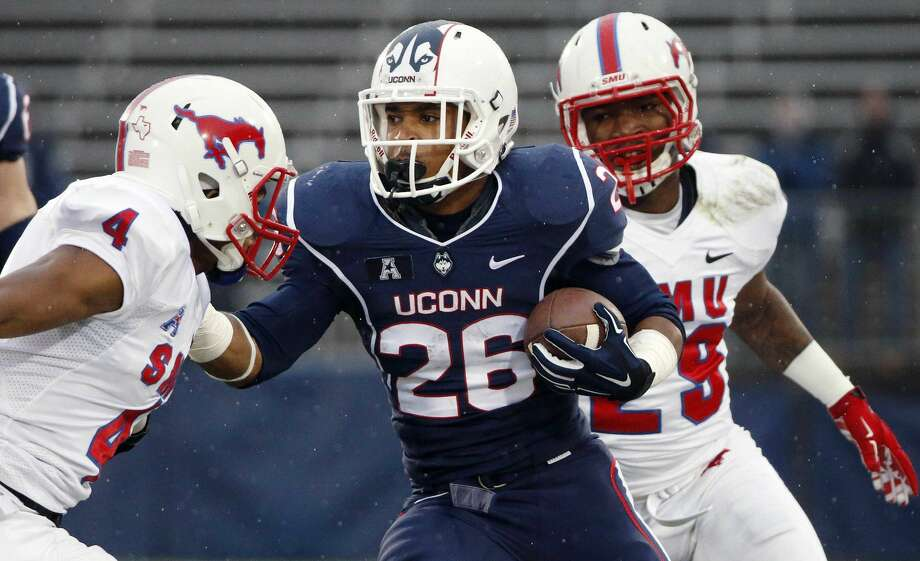 Connecticut running back Joshua Marriner (26) carries the ball against SMU defensive back Collin LaGasse (4) and defensive back Darrion Richardson (29) during the second quarter of an NCAA college football game in East Hartford, Conn., Saturday, Dec. 6, 2014. (AP Photo/Michael Dwyer)