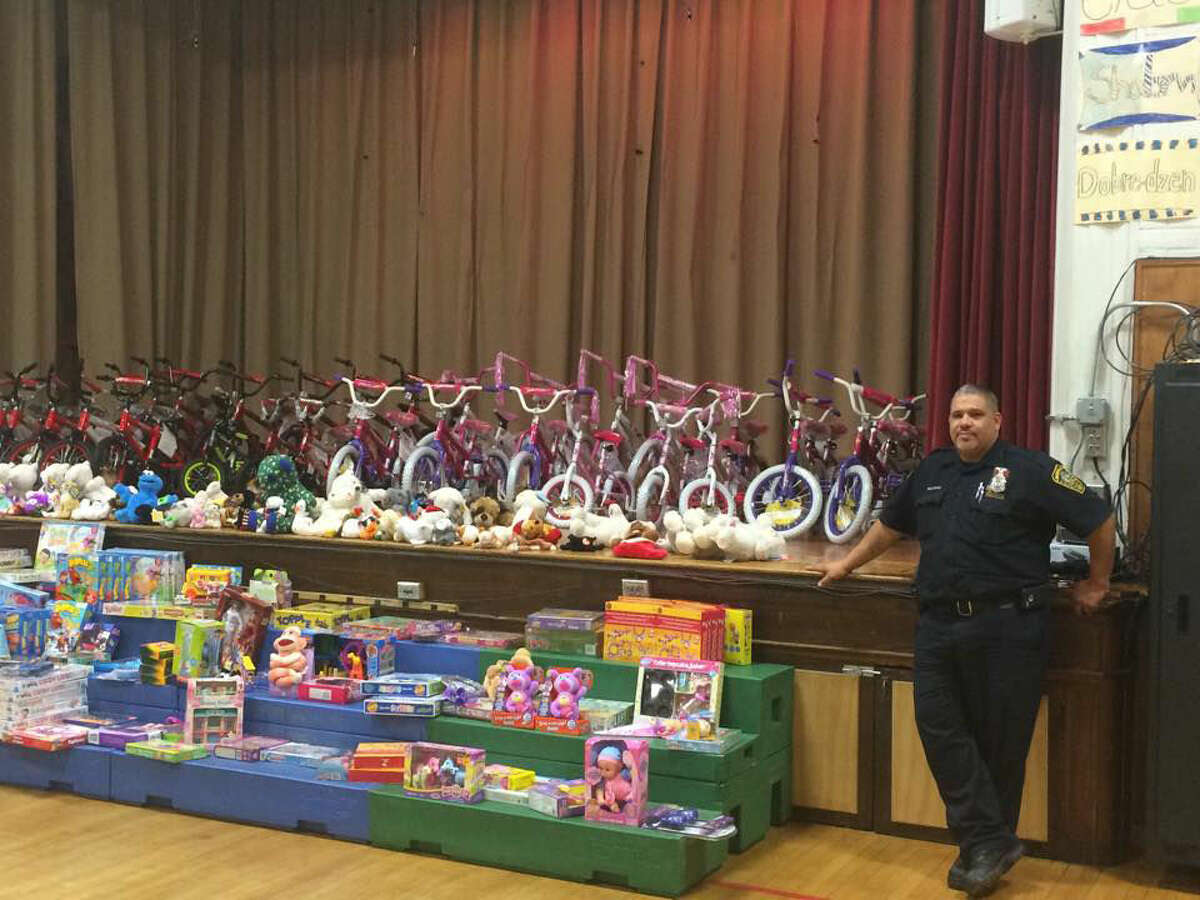 Contributed photo Norwalk Police Officer Hector Delgado stands in front of a handful of gifts given to local kids at the Norwalk Police Athletic League's annual holiday party Saturday at Columbus Magnet School.