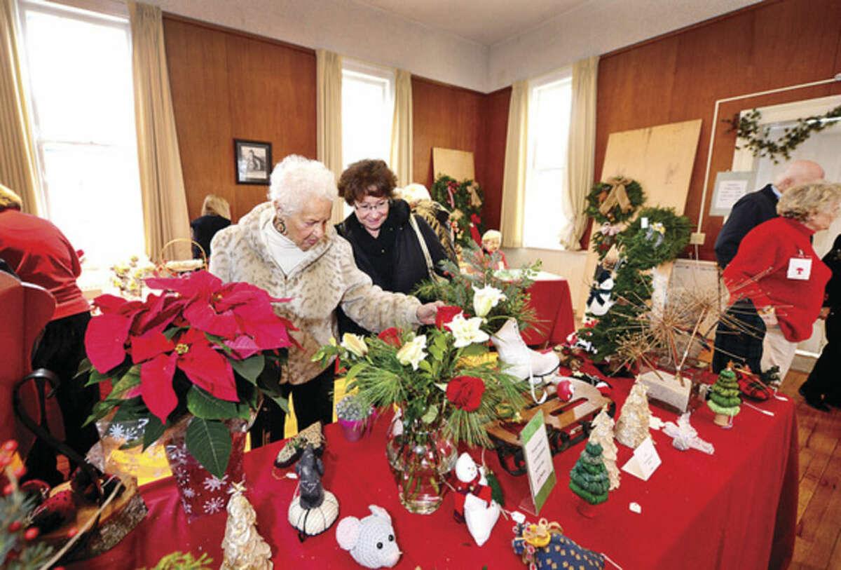 Hour photo/Erik Trautmann Virginia Finnie and her daughter Lori Viselli look for handmade items at Norwalk Garden Club's annual Christmas craft fair at Cranbury Chapel Saturday.