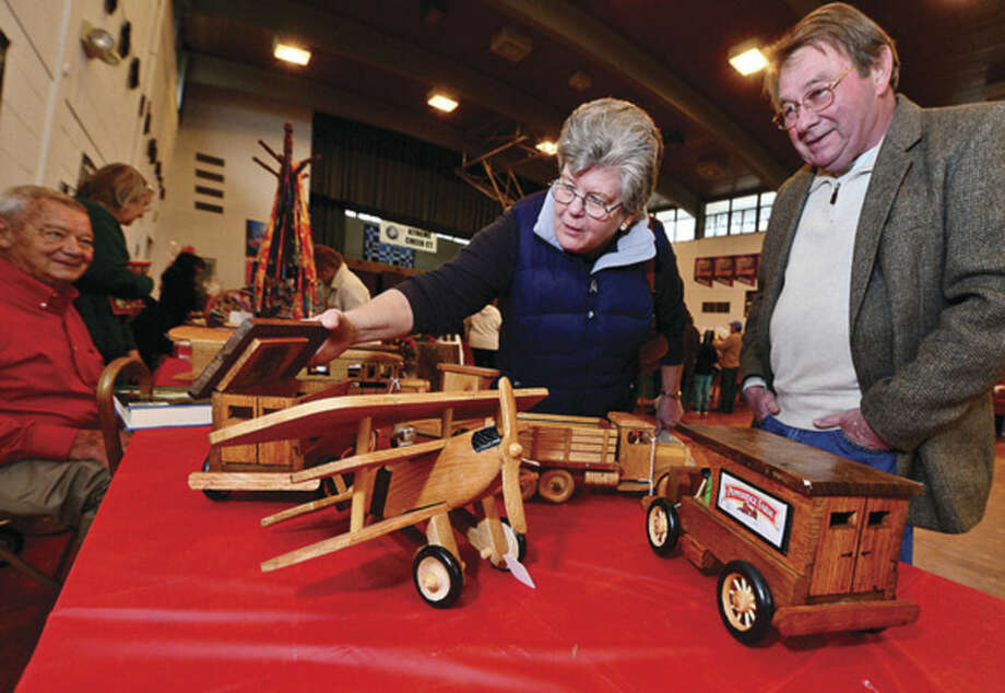 Hour photo / Erik TrautmannJean and Jack O'Neil look over the handmade wooden toys by Fred Anderson for sale at the St. Ladislaus annual Christmas fair Saturday.