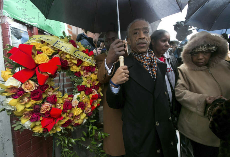 The Rev. Al Sharpton is accompanied by Esaw Garner, center, wife of Eric Garner, who died in a chokehold incident with a New York City Police officer, and Gwen Carr, mother of the deceased, as he places a wreath at the scene of the occurrence, in the Staten Island borough of New York, Saturday, Dec. 6, 2014. (AP Photo/Richard Drew)