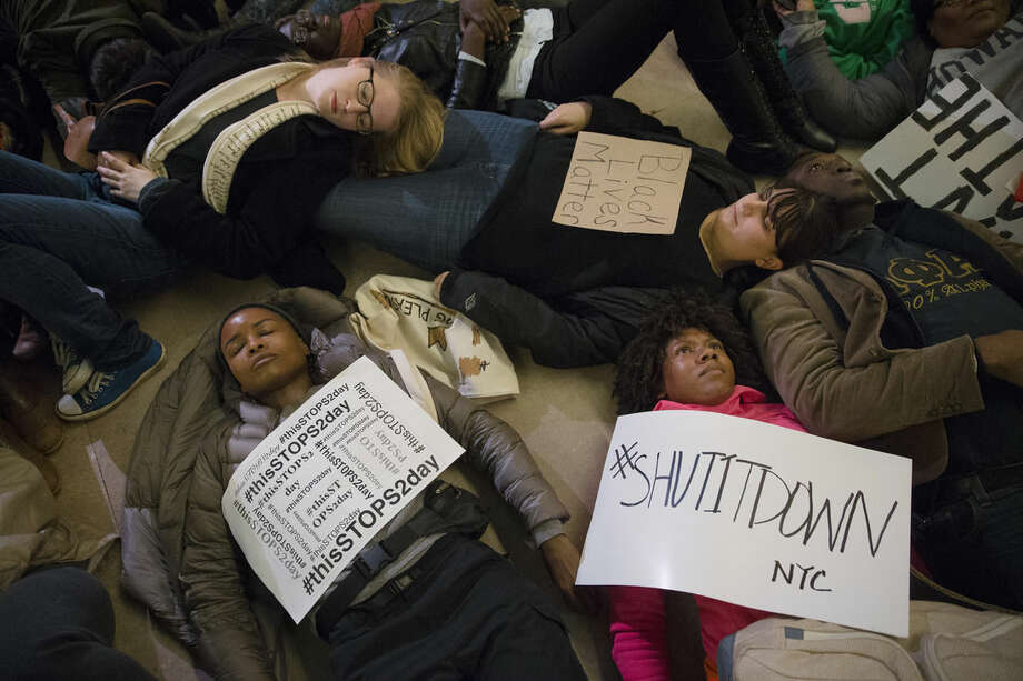 "Protesters participate in a ""die-in"" at Grand Central Station during a demonstration against a grand jury's decision not to indict the police officer involved in the death of Eric Garner, Saturday, Dec. 6, 2014, in New York. (AP Photo/John Minchillo)"