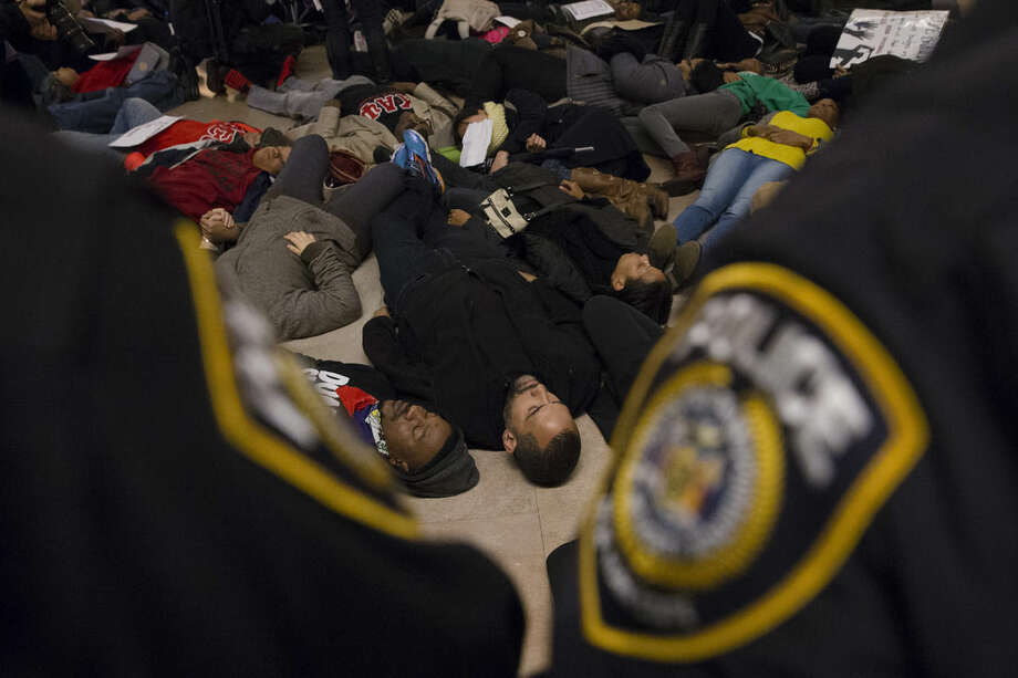 "Protesters participate in a ""die-in"" at Grand Central Station as police stand guard during a demonstration against a grand jury's decision not to indict the police officer involved in the death of Eric Garner, Saturday, Dec. 6, 2014, in New York. (AP Photo/John Minchillo)"