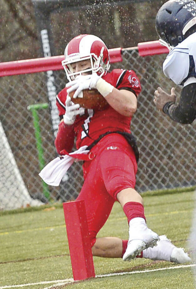 Hour photo / Erik Trautmann #7, Alexander LaPolice of New Canaan, comes down with a touchdown reception at the end of the first half during their state playoff against Westfield game Saturday.