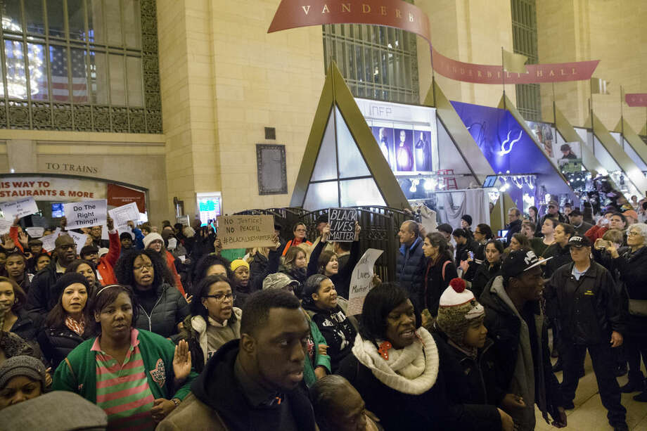 "Protesters march out of Grand Central Station after a ""die-in"" against a grand jury's decision not to indict the police officer involved in the death of Eric Garner, Saturday, Dec. 6, 2014, in New York. (AP Photo/John Minchillo)"