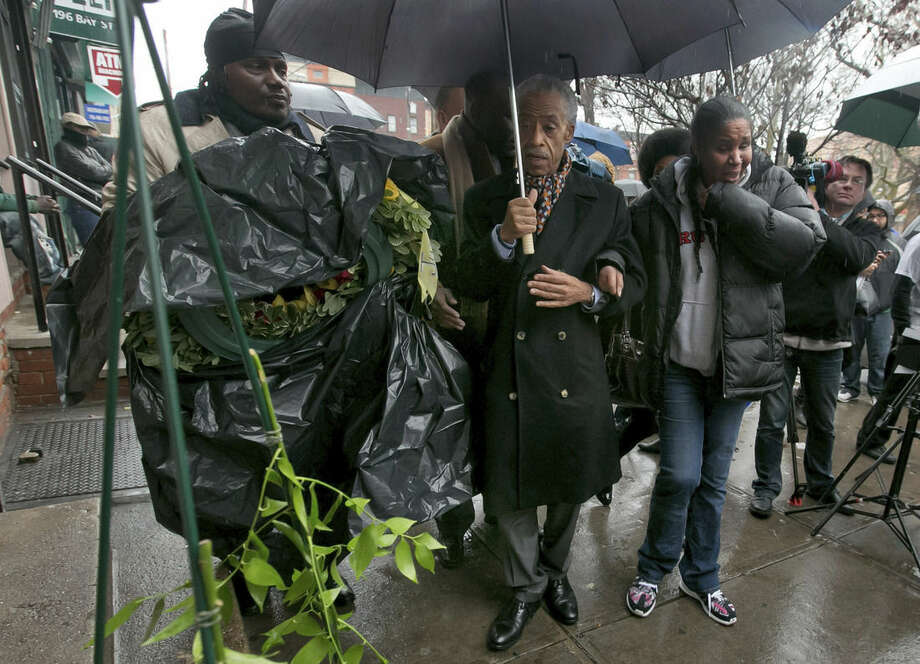 The Rev. Al Sharpton, center, is accompanied by Esaw Garner, wife of Eric Garner, who died in a chokehold incident with a New York City Police officer, as he arrives with a wreath at the scene of the occurrence, in the Staten Island borough of New York, Saturday, Dec. 6, 2014. (AP Photo/Richard Drew)