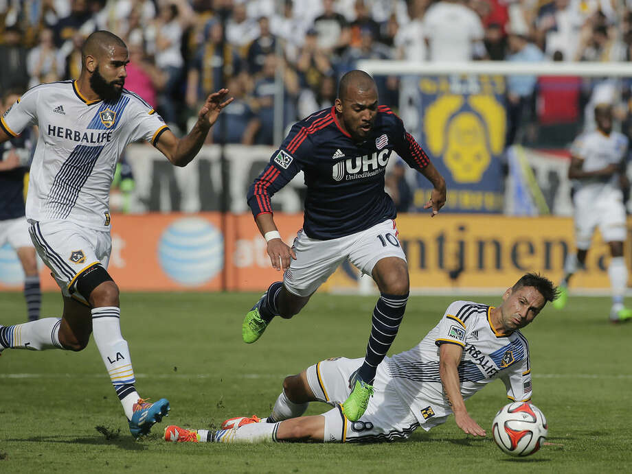 New England Revolution's Teal Bunbury, center, is tackled by Los Angeles Galaxy's Marcelo Sarvas, left, of Brazil, as Galaxy's Leonardo, also of Brazil, watches during the first half of the MLS Cup championship soccer match Sunday, Dec. 7, 2014, in Carson, Calif. (AP Photo/Jae C. Hong)