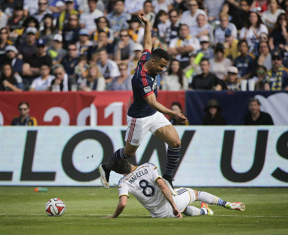 New England Revolution's Charlie Davies, top, jumps to avoid a tackle from Los Angeles Galaxy's Marcelo Sarvas, of Brazil, during the first half of the MLS Cup championship soccer match Sunday, Dec. 7, 2014, in Carson, Calif. (AP Photo/Jae C. Hong)