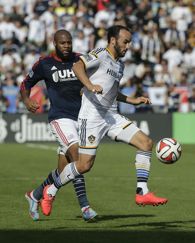 Los Angeles Galaxy's Landon Donovan, right, controls the ball past New England Revolution's Andrew Farrell during the first half of the MLS Cup championship soccer match Sunday, Dec. 7, 2014, in Carson, Calif. (AP Photo/Jae C. Hong)