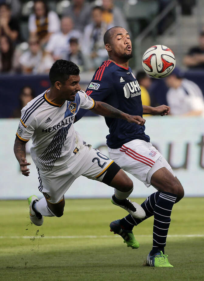 New England Revolution's Teal Bunbury, right, and Los Angeles Galaxy's A.J. DeLaGarza fight for the ball during the first half of the MLS Cup championship soccer match Sunday, Dec. 7, 2014, in Carson, Calif. (AP Photo/Jae C. Hong)