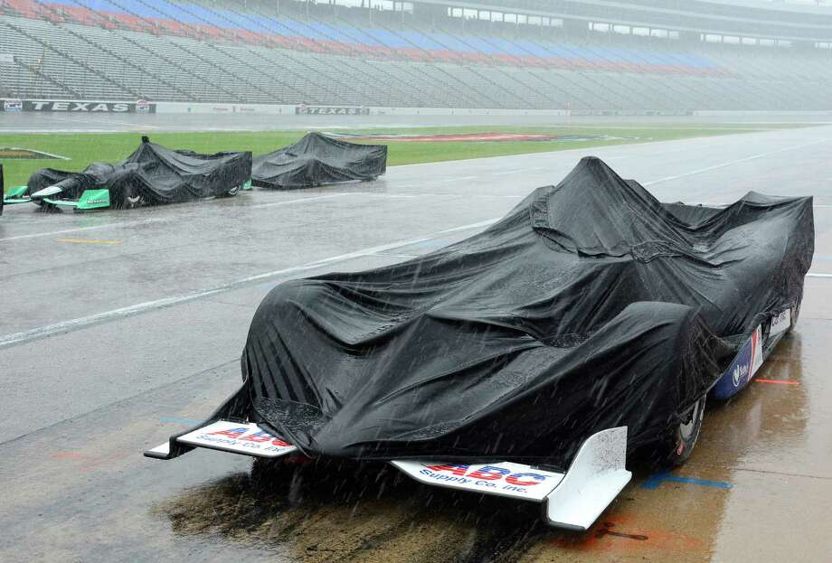 Race cars are covered by tarps during a thunderstorm which stopped an IndyCar auto race at Texas Motor Speedway, Sunday, June 12, 2016, in Fort Worth, Texas. (AP Photo/Larry Papke) Photo: Larry Papke, Associated Press / FR58581 AP