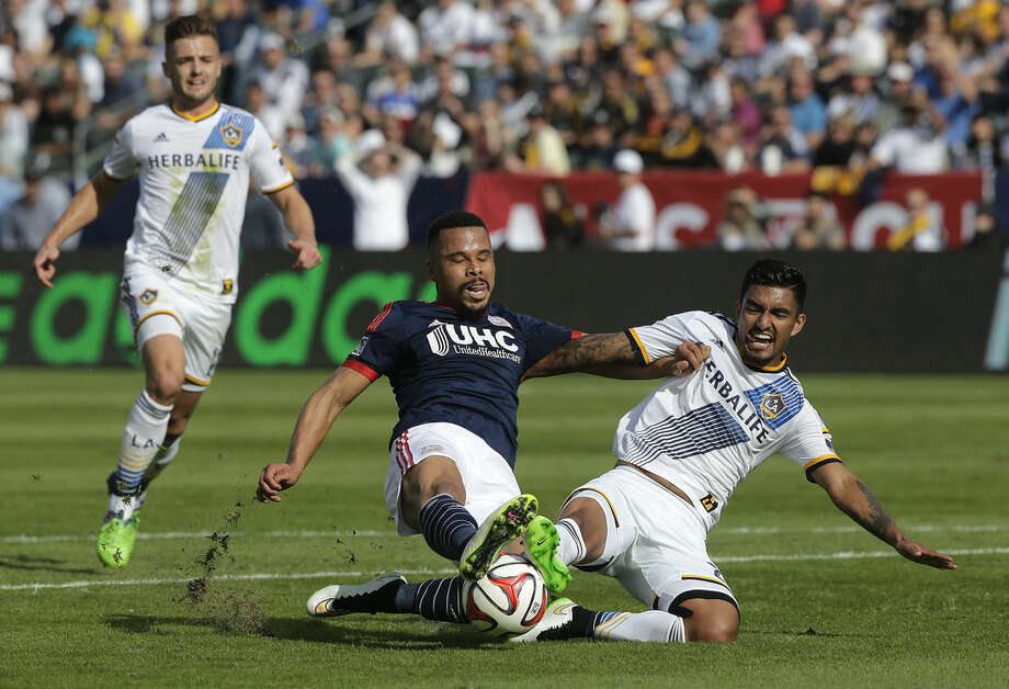 New England Revolution's Charlie Davies, center, is tackled by Los Angeles Galaxy's A.J. DeLaGarza during the first half of the MLS Cup championship soccer match Sunday, Dec. 7, 2014, in Carson, Calif. (AP Photo/Jae C. Hong)