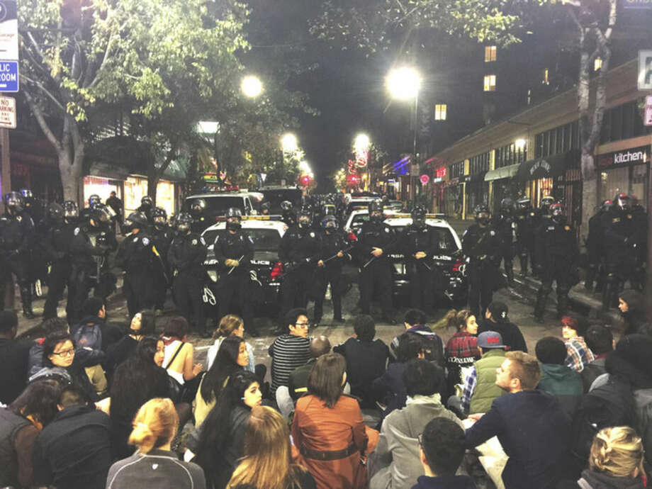 AP photo/Gabriel ReyesThis photo provided by Gabriel Reyes shows the protest in Berkeley, Calif., Sunday. Three officers and a technician were hurt and six people arrested in Northern California when a protest over police killings turned violent.