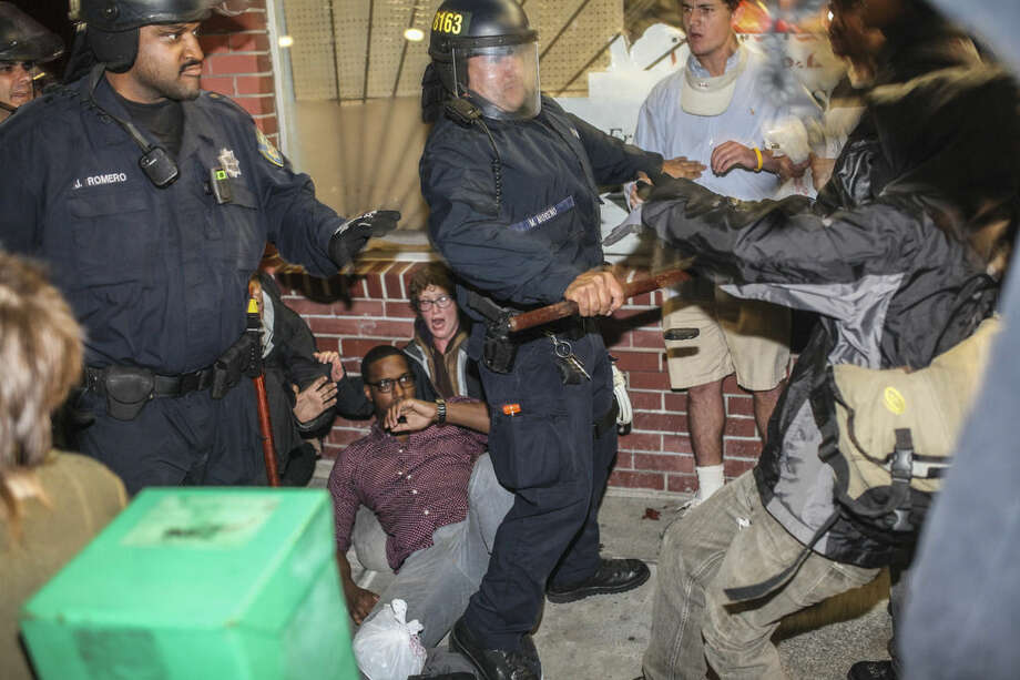 Demonstrators clash with police, in front of a man who injured his leg during the protest in Berkeley, California on Saturday, Dec. 6, 2014. Two officers were injured Saturday night as a California protest over police killings turned violent with protesters smashing windows and throwing rocks and bricks at police, who responded by firing tear gas, authorities said. Demonstrators were responding to the grand jury verdicts in the shooting death of Michael Brown in Ferguson, Missouri and the chokehold death of Eric Garner in New York City by local police officers in their communities. (AP Photo/San Francisco Chronicle, Sam Wolson)