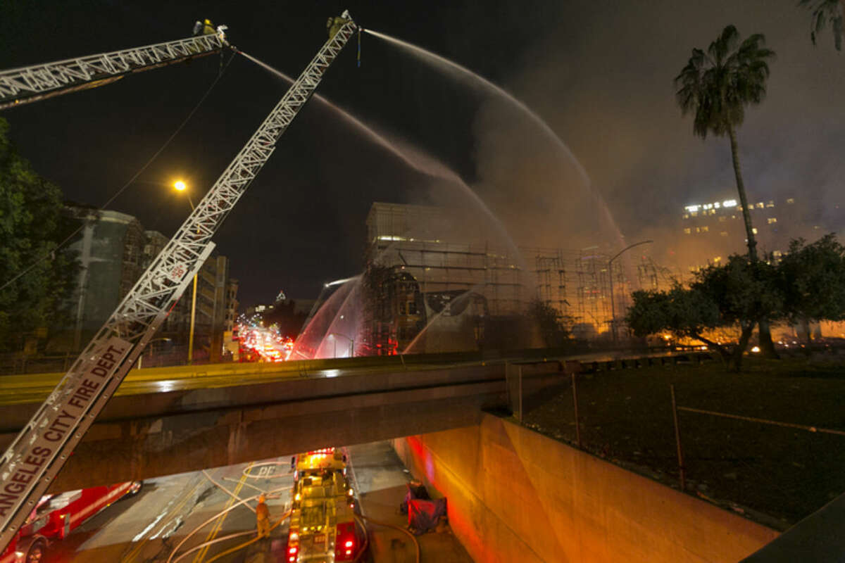 Los Angeles County firefighters battle a fire at an apartment building under construction next to the Harbor CA-110 Freeway in Los Angeles, early Monday, Dec. 8, 2014. The building was not occupied, the Los Angeles Fire Department reported. (AP Photo/Damian Dovarganes)