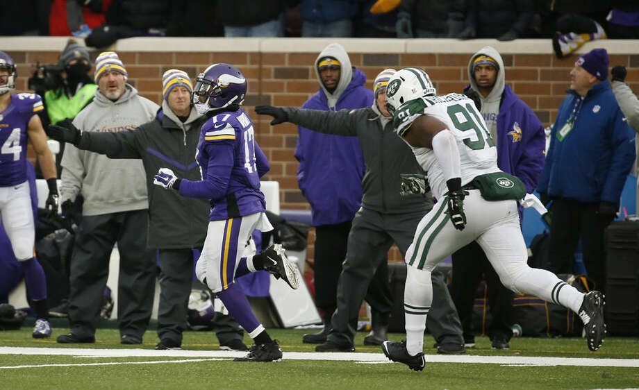 Minnesota Vikings wide receiver Jarius Wright, left, runs from New York Jets defensive end Sheldon Richardson during an 87-yard touchdown reception in overtime in an NFL football game, Sunday, Dec. 7, 2014, in Minneapolis. The Vikings won 30-24. (AP Photo/Alex Brandon)