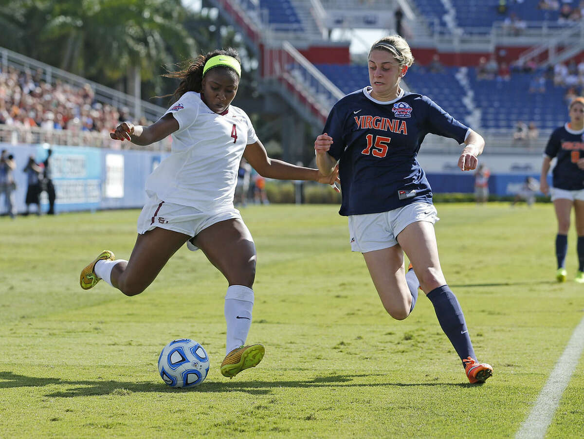 Florida State's Jamia Fields (4) brings the ball past Virginia's Tina Iordanou (15) during the first half of the women's NCAA soccer College Cup final in Boca Raton, Fla., Sunday, Dec. 7, 2014. (AP Photo/Joel Auerbach)