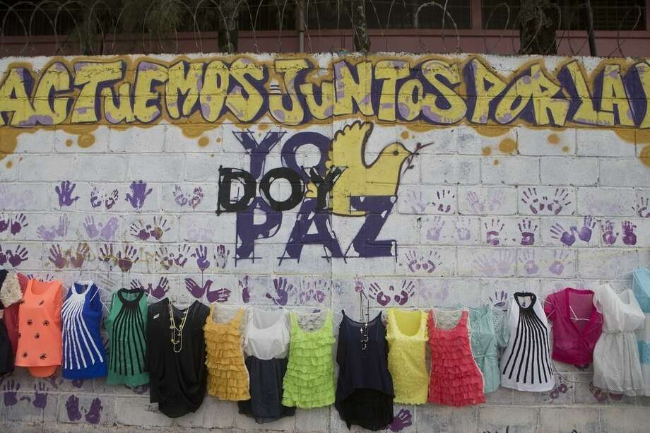 "In this Nov. 28, 2014 photo, women's clothing hangs for sale over a mural that reads in spanish ""Let's work together for peace,"" on the front wall of the Jose Ramon Montoya school in Tegucigalpa, Honduras. Last year, three students became pregnant after they were raped on the second floor of Montoya, according to a teacher. At the start of the new school year, officials called for protection, but when police tried to take control of the school, gangsters threw furniture at them from the second floor. Corrales said they then took a softer approach _ stationing officers at every door to keep a close eye on students. The gangsters retreated. (AP Photo/Esteban Felix)"