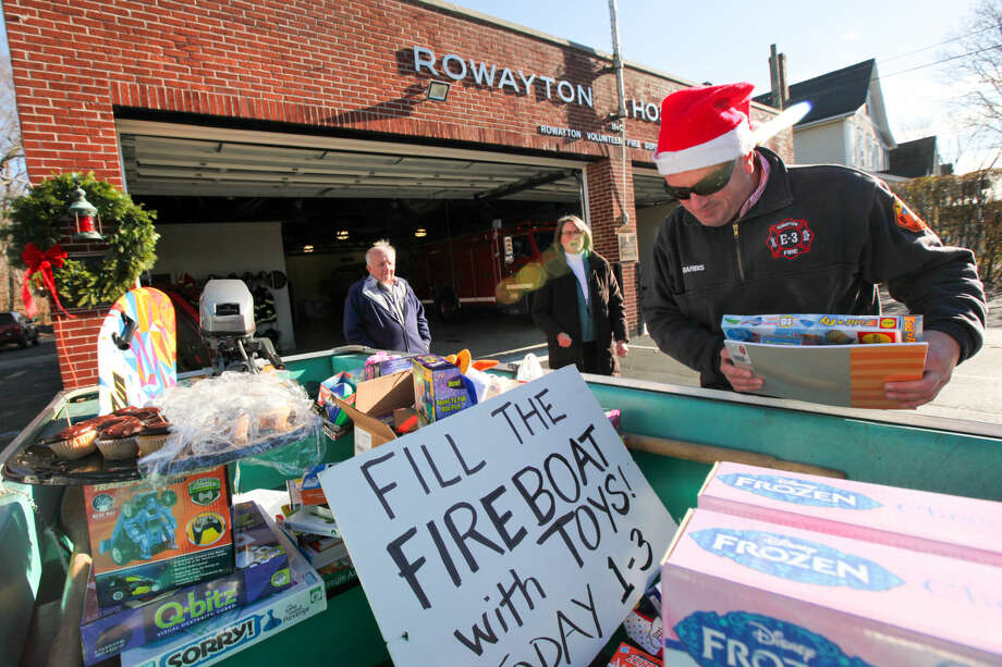 Hour photo/Chris Palermo. Rowayton Volunteer Firefighter Mike Barbis adds a gift donated by Megan St. John to the fire boat Sunday afternoon.