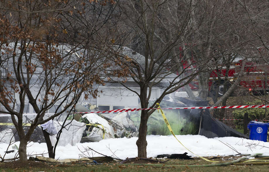 AP Photo/Jose Luis MaganaA small plane smolders after crashing into a house in Gaithersburg, Md., Monday Dec. 8. The small, private jet crashed into a house in Maryland's Montgomery County, and a fire official says at least three people on board were killed.