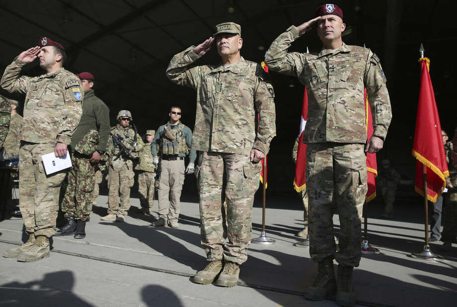 International Security Assistance Force Joint Command (IJC), Lieutenant General Joseph Anderson, right, and commander of International Security Assistance Force, General John F. Campbell, center, salute during a flag-lowering ceremony in Kabul, Afghanistan, Monday, Dec. 8, 2014. The U.S. and NATO ceremonially ended their combat mission in Afghanistan on Monday, 13 years after the Sept. 11 terror attacks sparked their invasion of the country to topple the Taliban-led government. From Jan. 1, the coalition will maintain a force of 13,000 troops in Afghanistan, down from a peak around 140,000 in 2011. There are around 15,000 troops now in the country.(AP Photo/Massoud Hossaini)