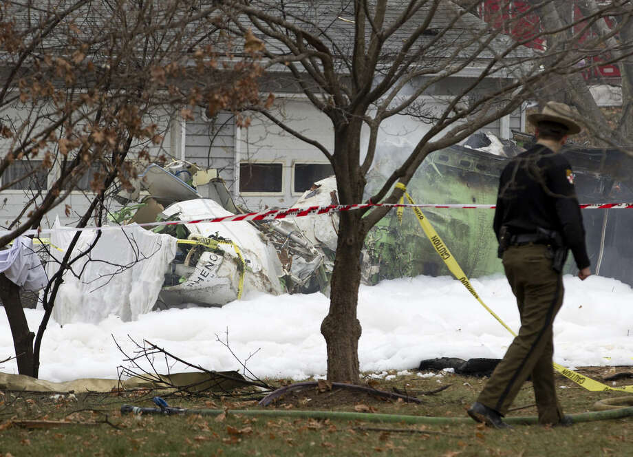 The wreckage of a small plane smolders in a house driveway after crashing in Gaithersburg, Md., Monday Dec. 8, 2014. The small, private jet has crashed into a house in Maryland's Montgomery County, and a fire official says at least three people on board were killed. (AP Photo/Jose Luis Magana)