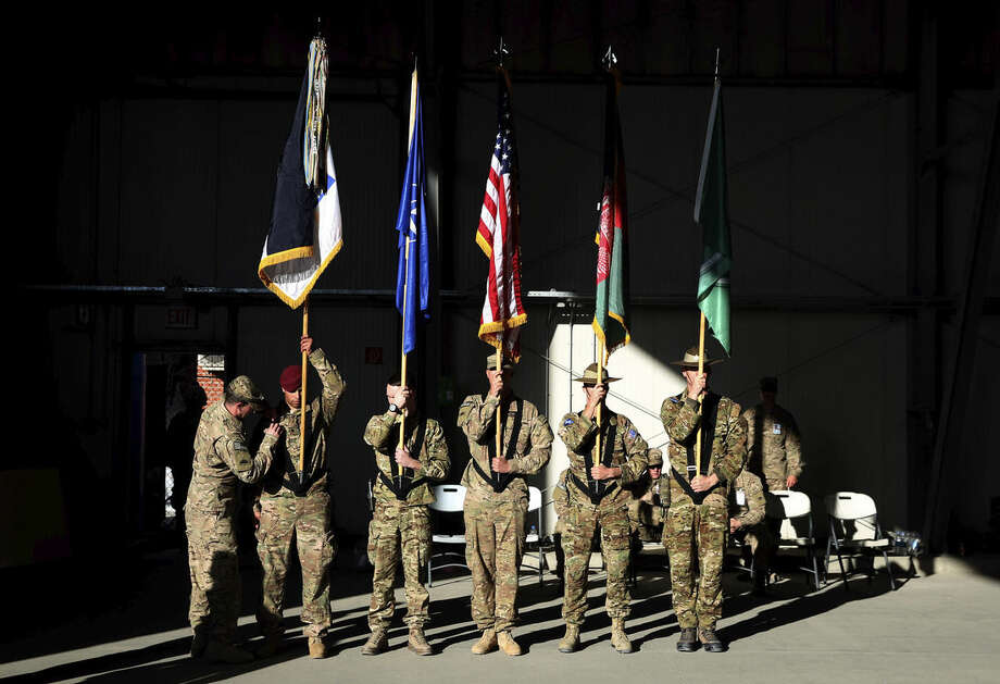 International Security Assistance Forces honor guards take part in a flag-lowering ceremony in north of Kabul International Airport in Kabul, Afghanistan, Monday, Dec. 8, 2014. The U.S. and NATO ceremonially ended their combat mission in Afghanistan on Monday, 13 years after the Sept. 11 terror attacks sparked their invasion of the country to topple the Taliban-led government. From Jan. 1, the coalition will maintain a force of 13,000 troops in Afghanistan, down from a peak around 140,000 in 2011. There are around 15,000 troops now in the country.(AP Photo/Massoud Hossaini)