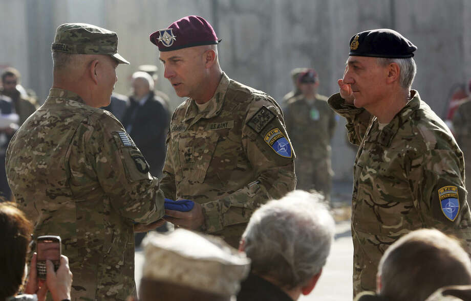 International Security Assistance Force Joint Command (IJC), Lieutenant General Joseph Anderson, center, hands over the flag of the IJC to commander of International Security Assistance Force, General John F. Campbell, left, a ceremony in north of Kabul International Airport in Kabul, Afghanistan, Monday, Dec. 8, 2014. The U.S. and NATO ceremonially ended their combat mission in Afghanistan on Monday, 13 years after the Sept. 11 terror attacks sparked their invasion of the country to topple the Taliban-led government. From Jan. 1, the coalition will maintain a force of 13,000 troops in Afghanistan, down from a peak around 140,000 in 2011. There are around 15,000 troops now in the country.(AP Photo/Massoud Hossaini)