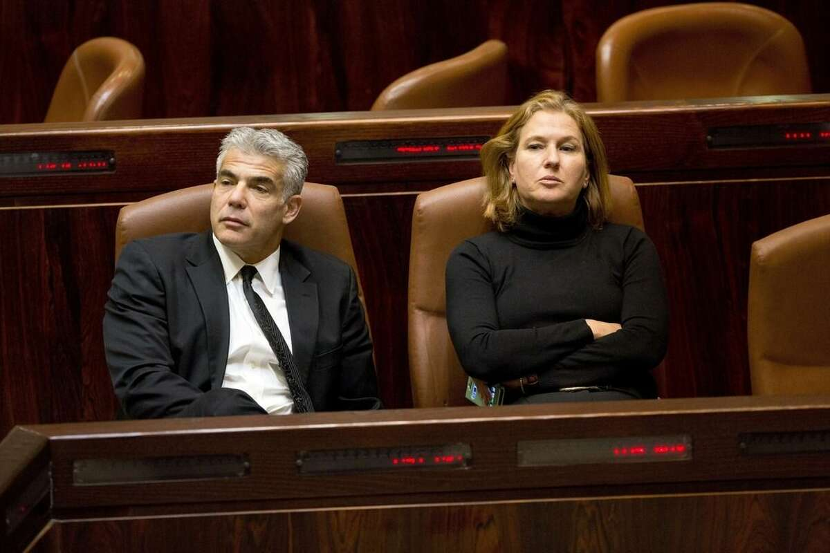 Israeli Finance Minister Yair Lapid, left, and Justice Minister Tzipi Livni sit following a vote at the Knesset, Israel's parliament in Jerusalem, Wednesday, Dec. 3, 2014. Israeli lawmakers voted Wednesday to dissolve the Knesset, a preliminary step that will pave the way for early elections two years ahead of schedule. (AP Photo/Sebastian Scheiner)