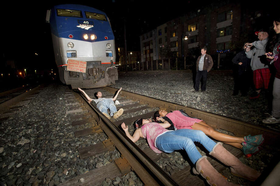 Protesters block an Amtrak train in Berkeley, Calif., on Monday, Dec. 8, 2014. Hundreds of people marched through Berkeley for a third night a row, blocking an interstate highway and stopping a train as activists rallied against grand jury decisions not to indict white police officers in the deaths of two unarmed black men. (AP Photo/Noah Berger)