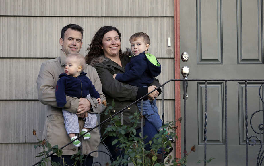 In this photo taken Wednesday, Oct. 15, 2014, Jennifer Ewing, and her husband Florian Thiel hold their children Max, 3, right, and Felix, 8-months, as they pose for a photo on the steps of their new home in Seattle's Ballard neighborhood. The couple recently closed on the three-bedroom house , which cost slightly less than $500,000. They moved to Seattle from New York, another city that matches the pattern of high-income jobs and even more expensive housing. (AP Photo/Elaine Thompson)