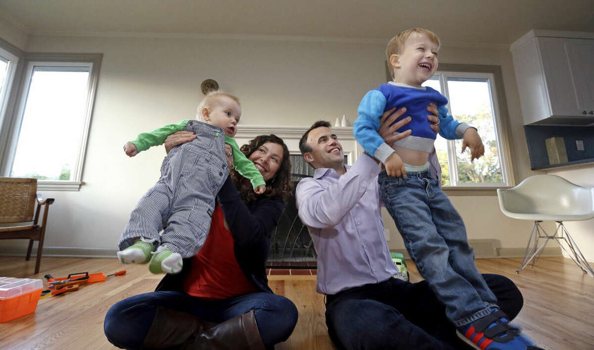 In this photo taken Wednesday, Oct. 15, 2014, Jennifer Ewing, second left, and her husband Florian Thiel playfully lift their children Max, 3, right, Felix, 8-months, as they sit for a photo on the floor of their new home in Seattle's Ballard neighborhood. The couple recently closed on the three-bedroom house, which cost slightly less than $500,000. They moved to Seattle from New York, another city that matches the pattern of high-income jobs and even more expensive housing. (AP Photo/Elaine Thompson)