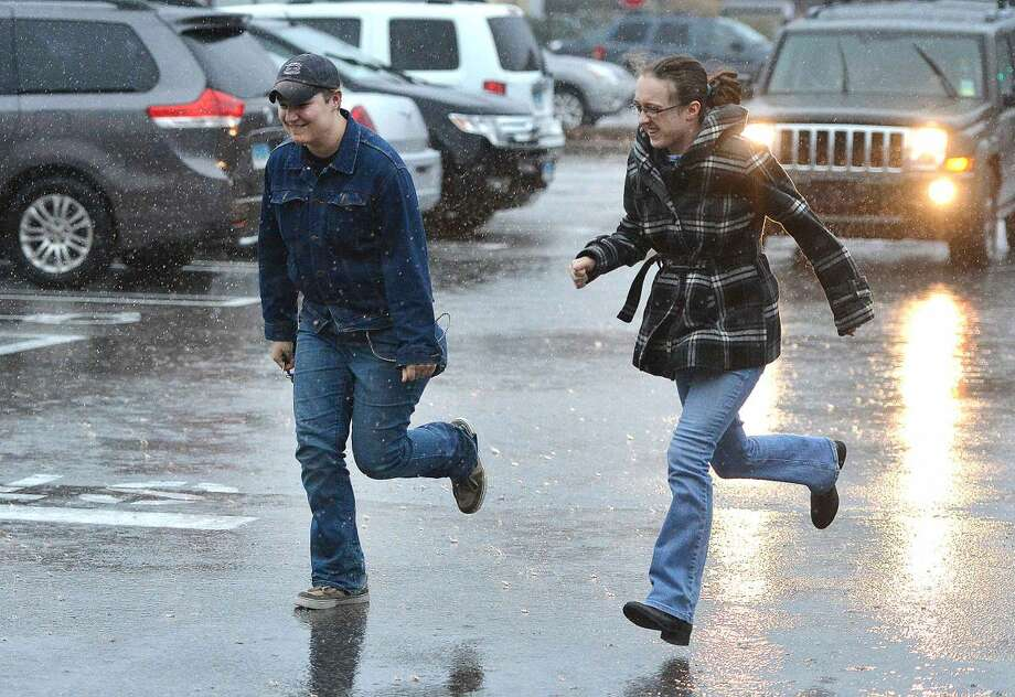 Hour Photo/Alex von Kleydorff People make their way into the Stop and Shop Plaza on Main Ave. during Tuesday's heavy rain