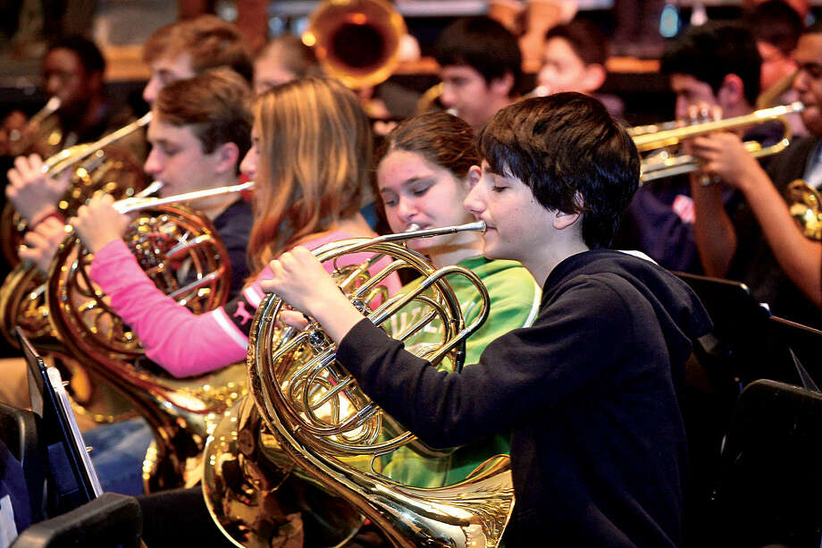 Hour photo / Erik Trautmann Brien McMahon High School choir, orchestra and band including french hornist Joseph Guarna rehearse for its annual Poinsettia winter concert.