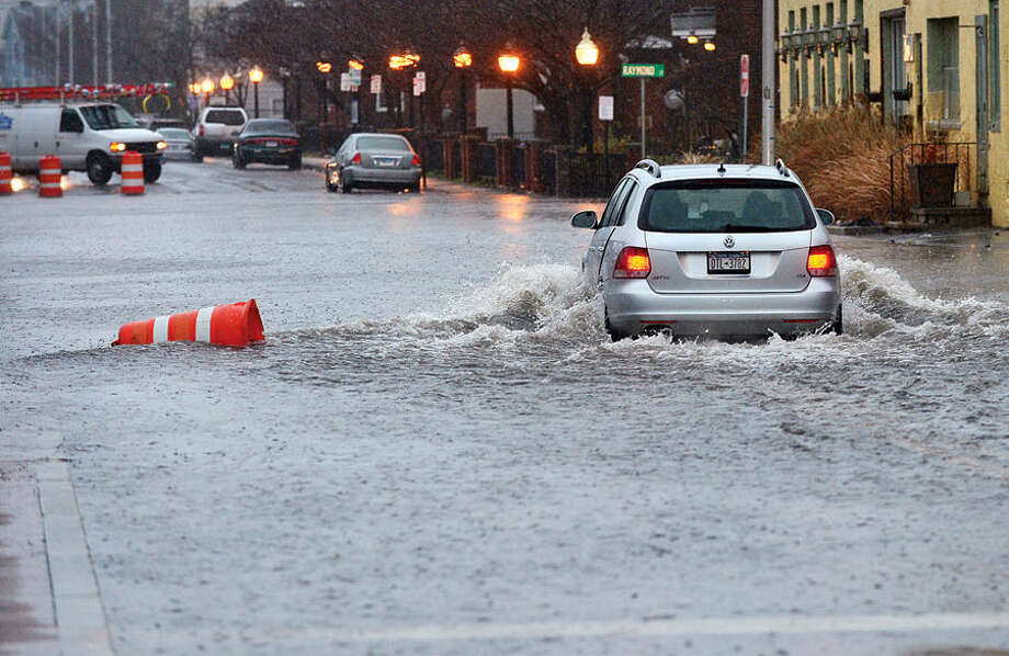 Hour photo / Erik Trautmann Heavy rains and a high tide Tuesday floods Water Street in South Norwalk.