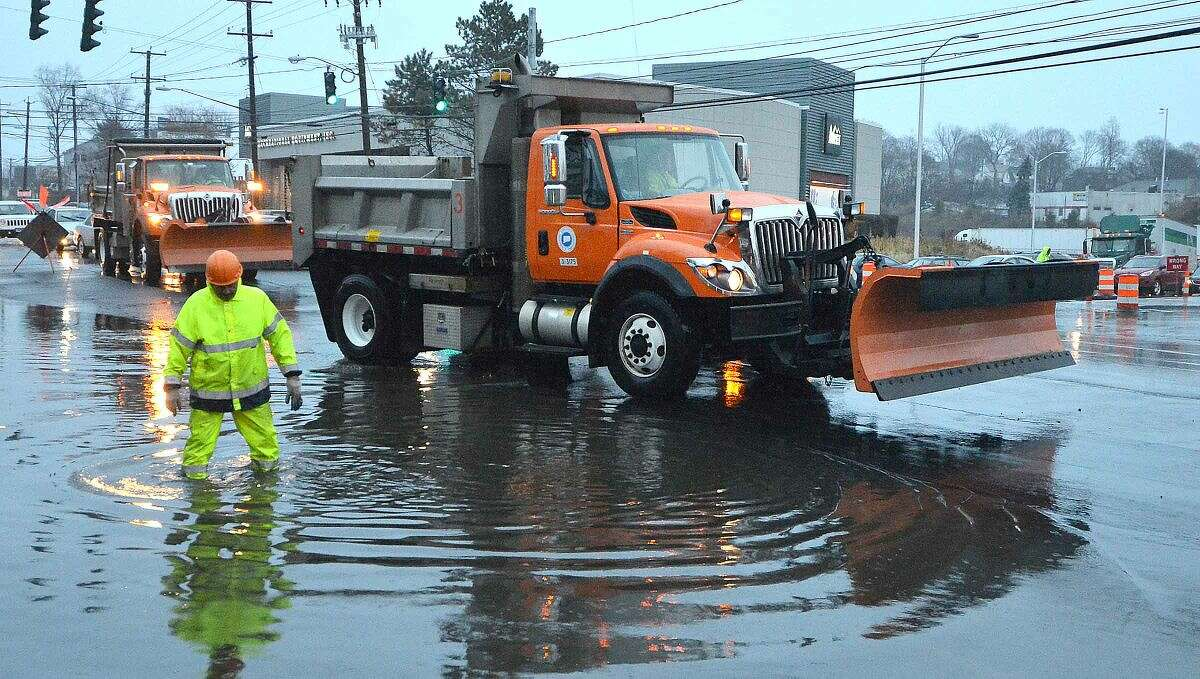 Hour Photo/Alex von Kleydorff State DOT Crews work on clearing a flooded Connecticut Ave at the I95 Soutbound exit ramp using snowplows to clear the more than foot deep water during Tuesday's Nor'easter