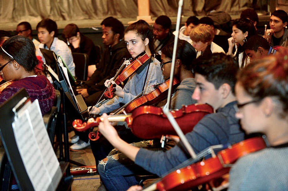 Hour photo / Erik Trautmann Brien McMahon High School choir, orchestra and band including violinist Jackie Aguiar rehearse for its annual Poinsettia winter concert.