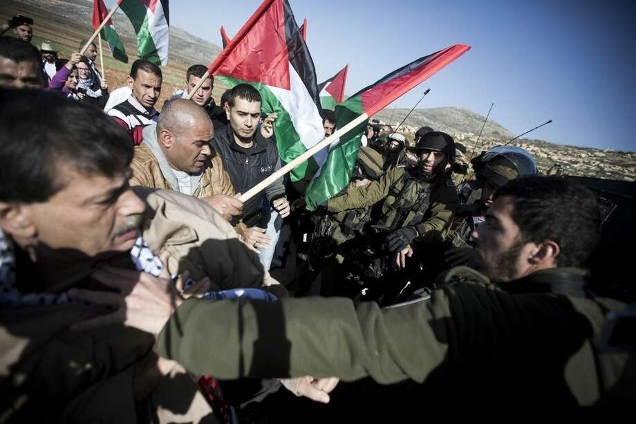 An Israeli soldier pushes Palestinian Cabinet member Ziad Abu Ain, left, during a protest in the village of Turmus Aya near the West Bank city of Ramallah, Wednesday, Dec. 10, 2014. Abu Ain died shortly after the protest in which witnesses said Israeli troops fired tear gas at him and dozens of Palestinians marchers. Witnesses also said Abu Ain, was beaten by an Israeli soldier. (AP Photo/Majdi Mohammed)