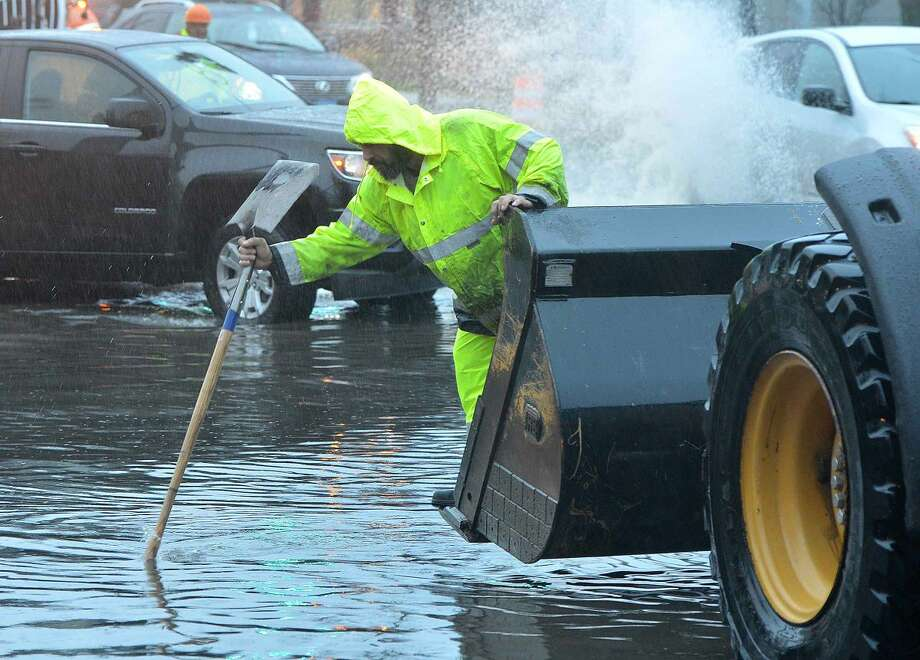 Hour Photo/Alex von Kleydorff Finding the storm drain the old fashioned way as State DOT Crews work on clearing a flooded Connecticut Ave at the I95 Soutbound exit ramp using snowplows to clear the more than foot deep water during Tuesday's Nor'easter