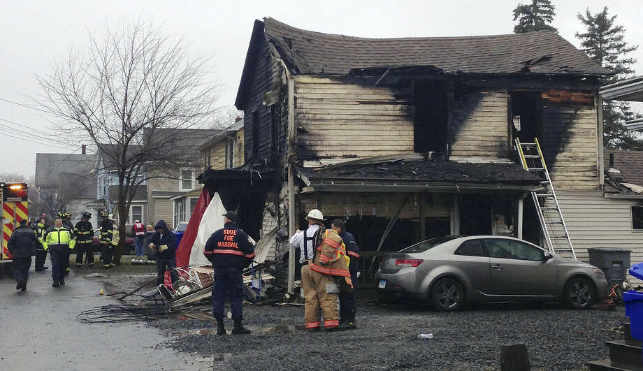 Firefighters work at the scene of a fire Wednesday morning, Dec. 10, 2014, at a two-family home in Enfield, Conn. Officials said at least four people were unaccounted for. (AP Photo/Dave Collins)