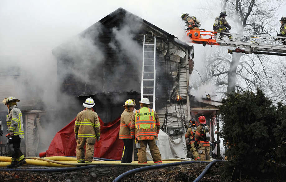 Firefighters control a house fire where four people were reportedly unaccounted for, Wednesday, Dec. 10, 2014, in Enfield, Conn., about 20 miles northeast of Hartford. (AP Photo/Journal Inquirer, Jessica Hill) MANDATORY CREDIT