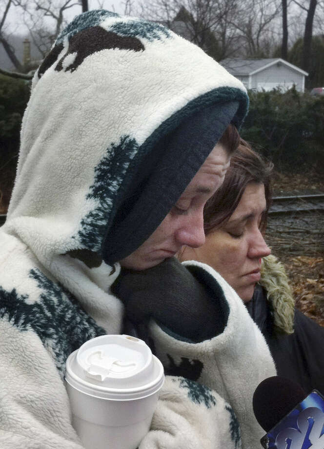 Jessica Rozalski, left, a family friend, and Dana Graham, right, look down while talking to reporters at the scene of a fire Wednesday morning, Dec. 10, 2014, at a two-family home in Enfield, Conn. Officials said at least four people were unaccounted for. (AP Photo/Dave Collins)