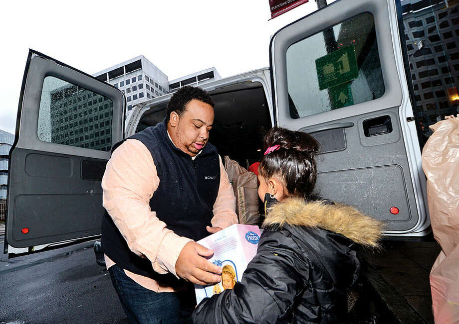 Hour photo / Erik Trautmann James Kendall and Nilah Palermo, 6, of the Stamford Boys and Girls Club help NBCUniversal executives and employees load up a van full of toys at the Stamford Media Center for distribution to children at the Boys & Girls Club. The toys were donated by NBCUniversal employees as part of the company's annual Holiday Toy Drive.