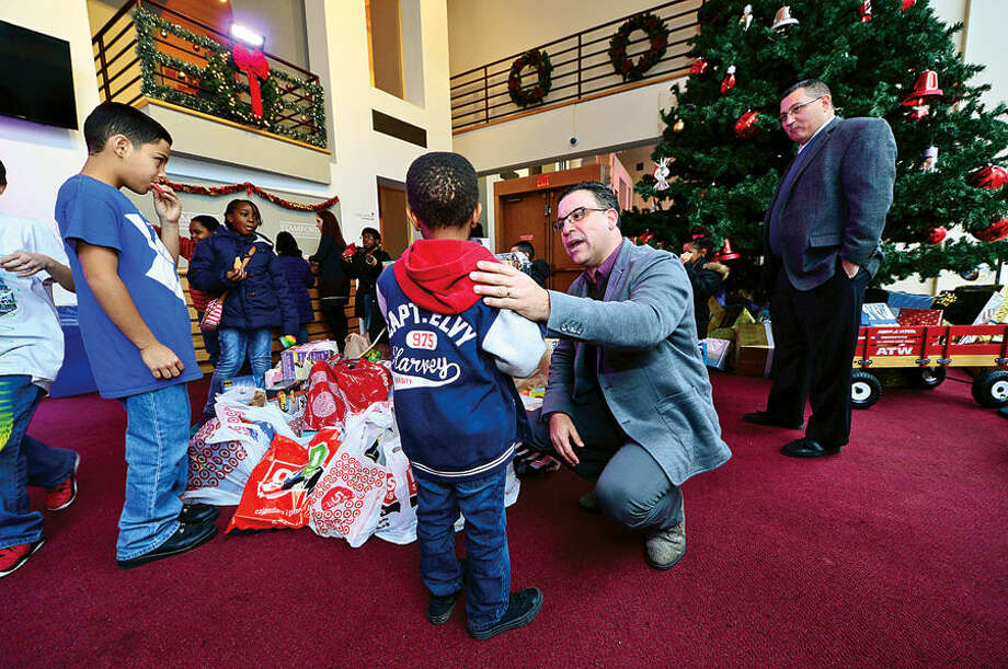 Hour photo / Erik Trautmann NBCUniversal and Stamford Media Center General Manager Vinnie Fusco chats with Jamir McIntosh, 6, at the Center as NBCUniversal executives and employees prepare to load up a van full of toys for distribution to children at the Boys & Girls Club of Stamford. The toys were donated by NBCUniversal employees as part of the company's annual Holiday Toy Drive.