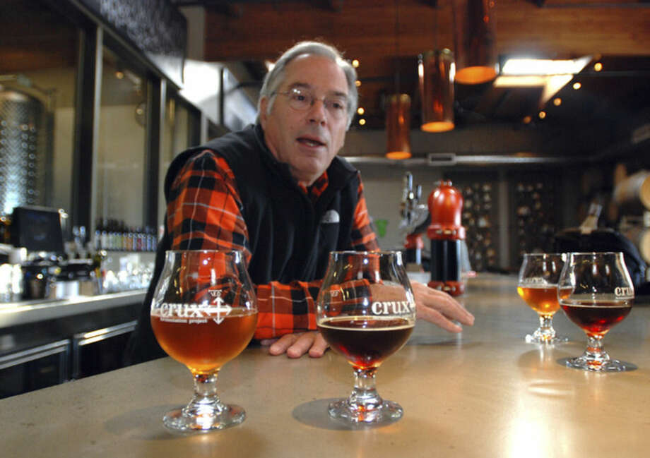 """In this Nov. 18, 2014 photo, brewmaster Larry Sidor discusses some of his creations at Crux Fermentation Project's brew pub in Bend, Ore. Sidor has been one of the brewers pushing the envelope on beer in Bend, which has seen an explosion of new breweries as the town has grown. One, 10 Barrel Brewing Co., recently announced it is being bought by Anheuser-Busch InBev, the world's largest brewer. Sidor worries that major corporations buying craft brewers will ultimately lead to the """"commoditization"""" of craft beer. (AP Photo/Jeff Barnard)"""