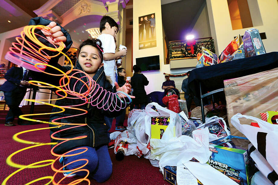 Hour photo / Erik Trautmann Nilah Palermo, 5, plays with a new slinky at the Stamford Media Center as NBCUniversal executives and employees prepare to load up a van full of toys for distribution to children at the Boys & Girls Club of Stamford. The toys were donated by NBCUniversal employees as part of the company's annual Holiday Toy Drive.