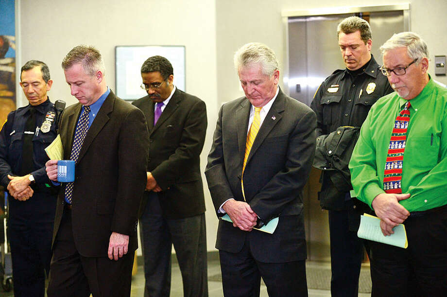 Hour photo / Erik Trautmann Norwalk mayor Harry Rilling, center, and other local officials observe a moment of silence during the 23rd annual International Human Rights Day at Norwalk City Hall.