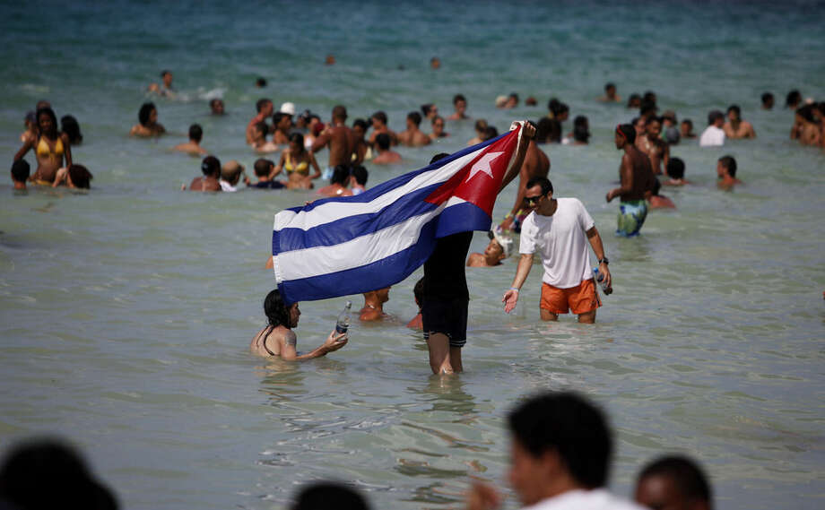 ADVANCE FOR USE THURSDAY, DEC. 11, 2014, AT 12:01 A.M. EST AND THEREAFTER- FILE- In this Aug. 6, 2014, file photo, a man waves a Cuban flag from the sea during the 12th annual Rotilla Festival in Jibacoa, Cuba. The festival had independent roots, but document show that Rajko Bozic and the EXIT festival had been backing it since 2006, a period during which it grew enormously. (AP Photo/Javier Galeano, File)